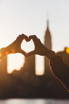 Heart shaped hands at sunset, new york skyline