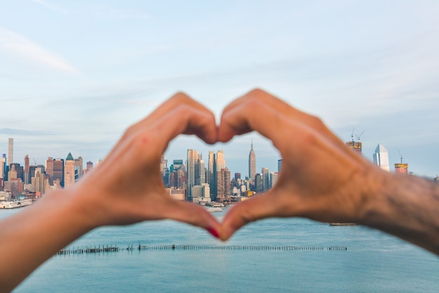 Heart shaped hands with new york skyline