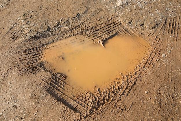 물과 타이어 휠로 땅에 하트 모양의 구멍이 있습니다.