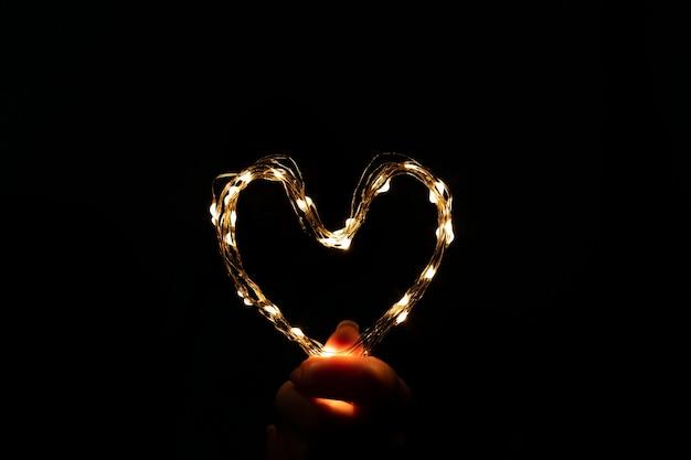 심장 모양의 여성 손에 휴가 축 하 빛 갈 랜드. 발렌타인 데이 개념입니다.