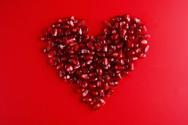 붉은 배경에 분리된 하트 모양의 육즙이 많은 석류 씨앗, 러브 가넷, 발렌타인 데이 컨셉