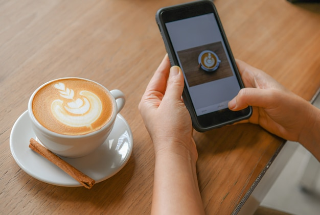 Heart-shaped latte coffee on a wooden table and people are preparing coffee pictures in mobile phone.