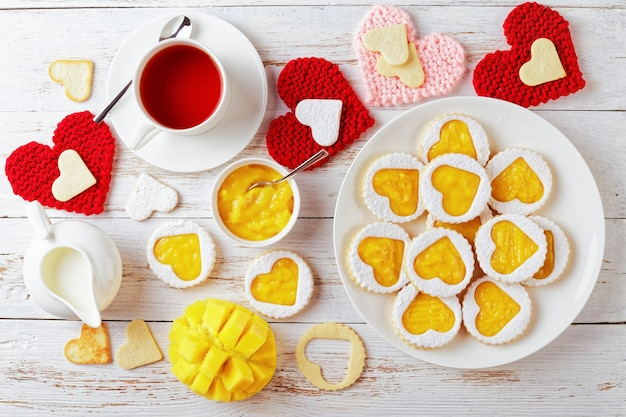 Линцерское печенье в форме сердца с манговым вареньем на белой тарелке на деревянном столе, украшенном красными и розовыми вязанными сердечками. чашка чая, манго и кувшин со сливками на столе, плоский