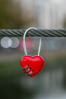 Heart shaped lock on on rope on urban street background.