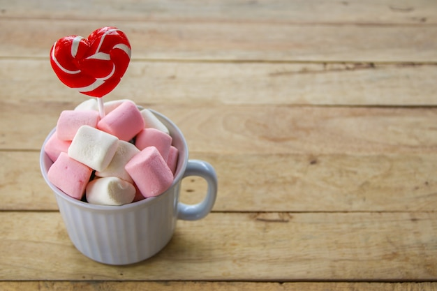 Heart shaped lollipop and marshmallow in white mug on wooden background.