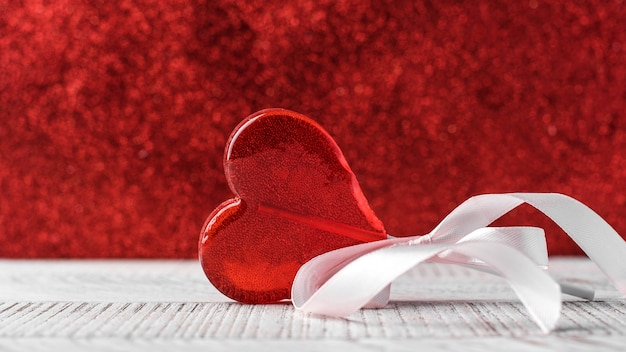 Heart-shaped lollipop on a red background. valentine's day background copy space