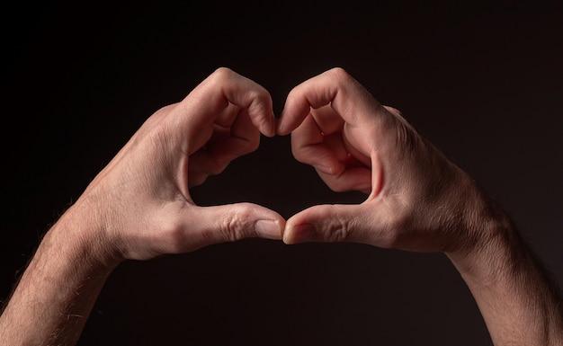 평화와 희망으로 하트 모양의 성숙한 남성의 손을 검정 배경 위에 서명합니다.
