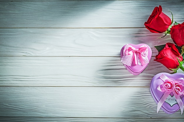 Металлические подарочные коробки в форме сердца с красными розами на деревянной доске, концепция праздников