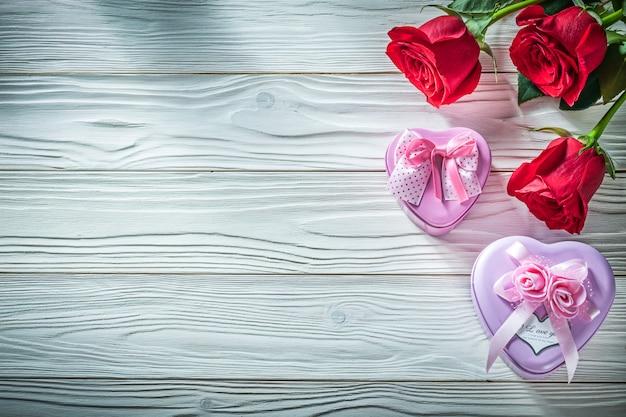 Металлические подарочные коробки в форме сердца из натуральных красных роз на деревянной доске