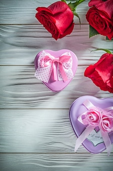 Heart-shaped metal present boxes natural red roses on wooden board