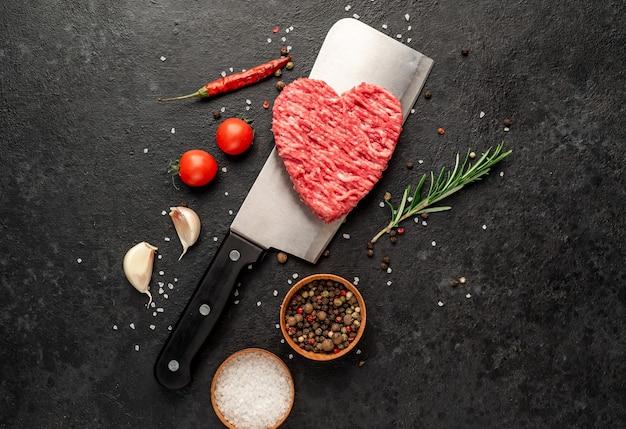 Фарш в форме сердца на ноже на каменном фоне