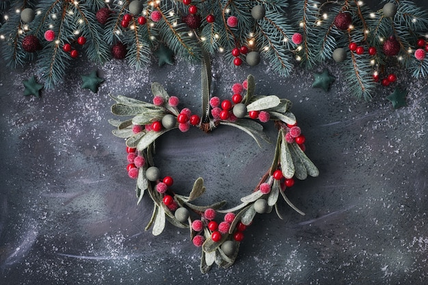 Heart-shaped mistletoe christmas wreath and festive garland made from fir twigs, frosted berries and trinkets