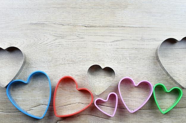 ハート型の型は木製のテーブルの上に置かれ、愛とバレンタインデーのデザインのためのコピースペースがあります。