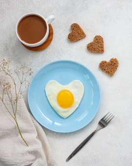 Heart shaped omelette on a light blue plate with coffee and bread
