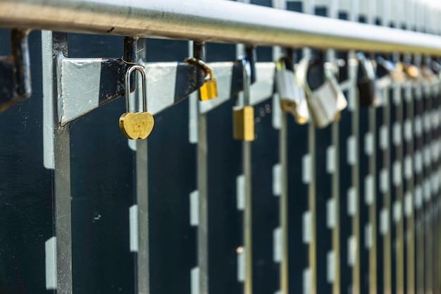 다른 잡색의 자물쇠 사이에 레일에 매달려 있는 하트 모양의 자물쇠.