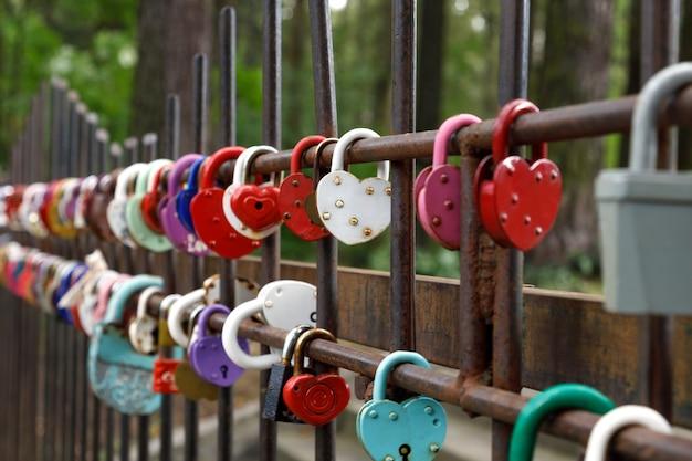 Навесные замки в форме сердца, висящие на заборе. выборочный фокус.