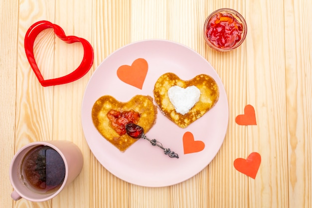 Heart shaped pancakes for romantic breakfast with strawberry jam and black tea