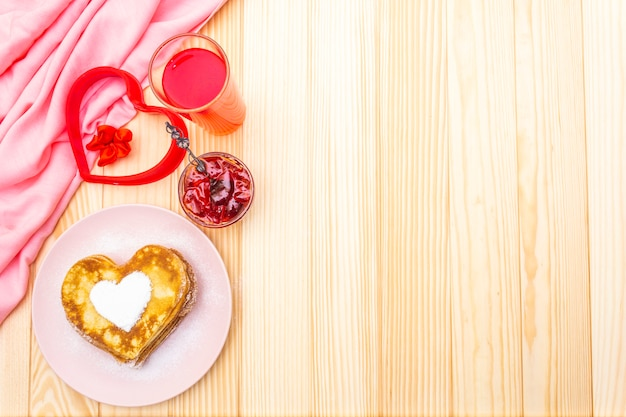 Heart shaped pancakes for romantic breakfast with strawberry jam and juice