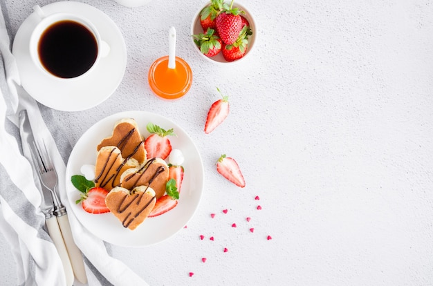 Heart-shaped pancakes with chocolate sauce and fresh strawberries
