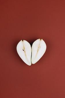 ダークバーガンディの背景にハート型の洋ナシの秋の構成上面図フラットレイクリエイティブ秋の愛...
