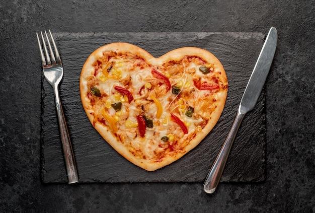 Пицца в форме сердца на день святого валентина на грифельной доске со столовыми приборами