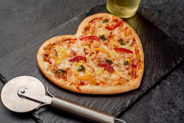 Пицца в форме сердца на день святого валентина на грифельной доске с ножом для пиццы