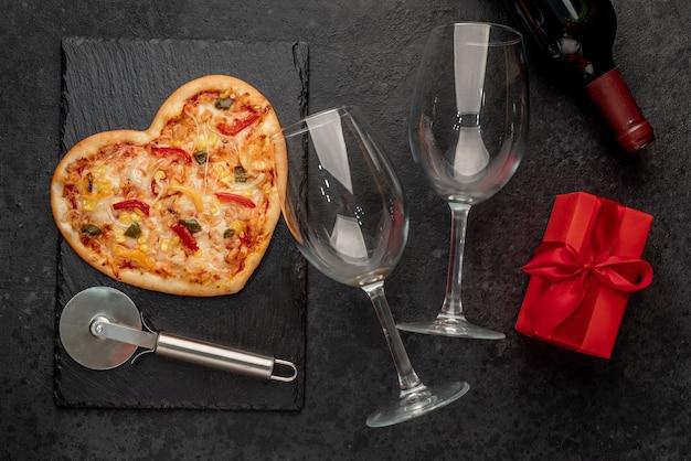 Пицца в форме сердца на день святого валентина с бутылкой вина и двумя бокалами на грифельной доске