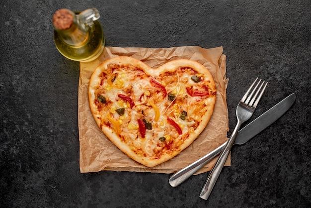 Пицца в форме сердца на день святого валентина со столовыми приборами и оливковым маслом