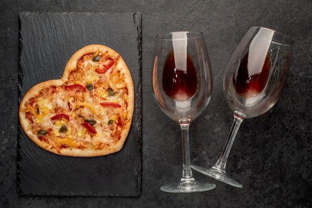 Пицца в форме сердца на день святого валентина с двумя стаканами на грифельной доске