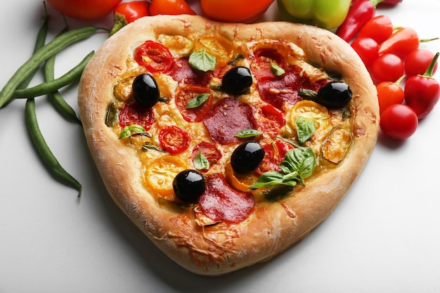 Heart shaped pizza and fresh vegetables isolated on white
