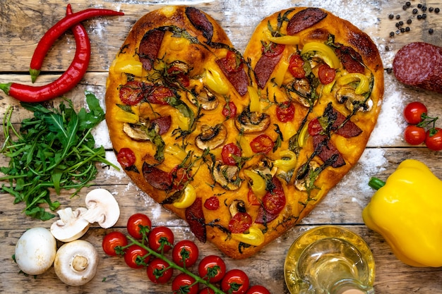 Heart-shaped pizza and ingredients for valentine's day, ready-made pizza, cooking process