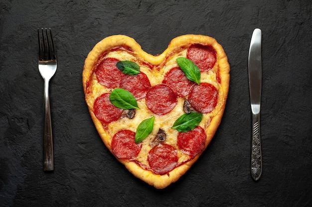 黒い石の上にハート型のピザ。バレンタインデーのロマンチックな愛の概念