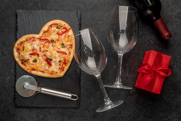 Heart-shaped pizza for valentines day with a bottle of wine and two glasses on slate