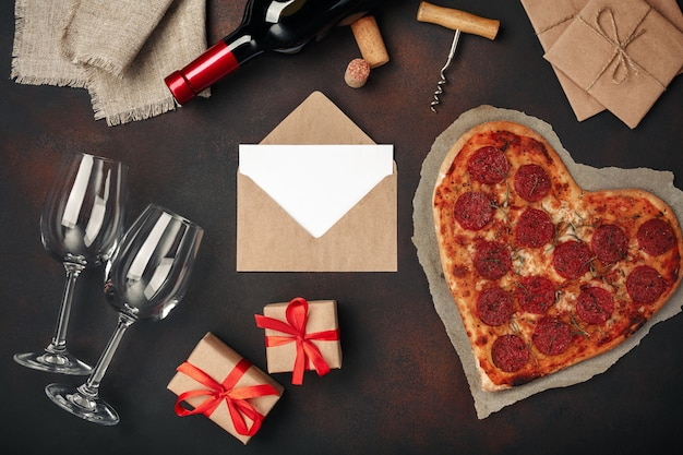 Heart shaped pizza with mozzarella, sausagered, wine bottle, two wineglass, gift box on rusty background