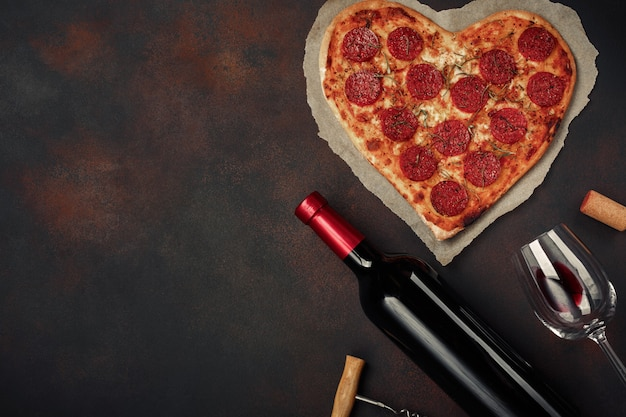 Heart shaped pizza with mozzarella, sausagered with a bottle of wine and wineglas on rusty background.