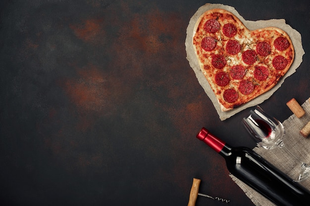 Heart shaped pizza with mozzarella, sausagered with a bottle of wine and wineglas. valentines day greeting card on rusty background