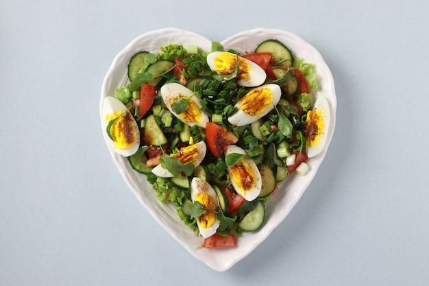 밝은 파란색 배경에 토마토, 오이, 계란, arugula 및 녹색 양파와 함께 건강한 샐러드와 하트 모양의 접시, 위에서보기