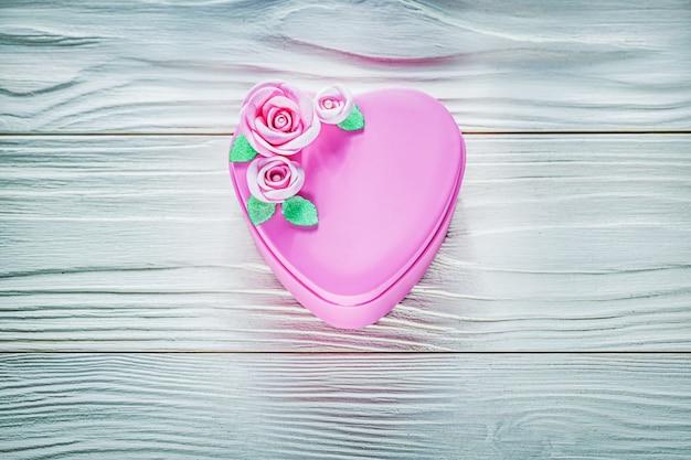 Подарочная коробка в форме сердца на концепции празднования деревянной доски