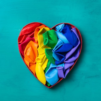 Heart shaped rainbow lgbtq flag against turquoise background pride month