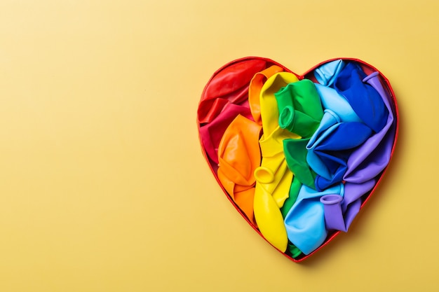 Heart shaped rainbow lgbtq flag against yellow background pride month