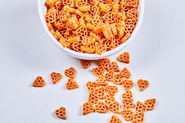 Сырые макароны в форме сердца на сером столе.