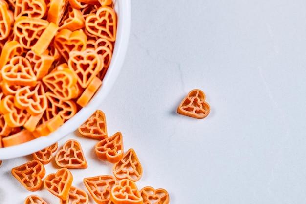 Сырые макароны в форме сердца на белом углу.