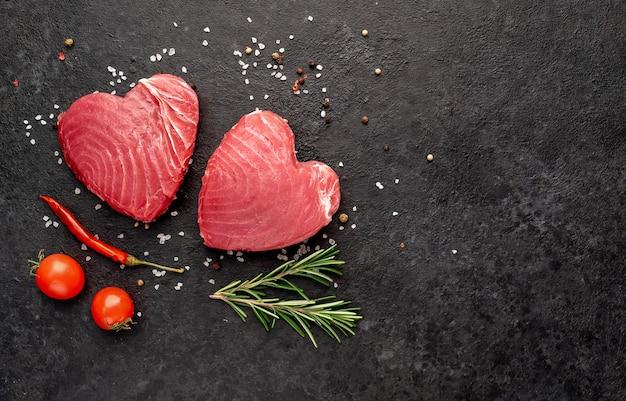Сырые стейки тунца с розмарином и специями на каменном фоне в форме сердца с местом для текста