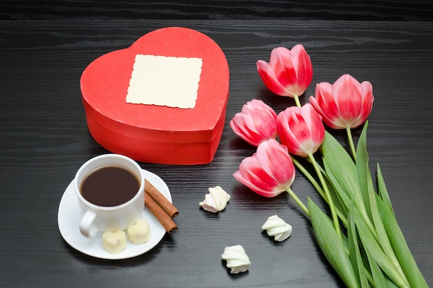 Heart shaped red box, pink tulips, gray sheet and coffee mug