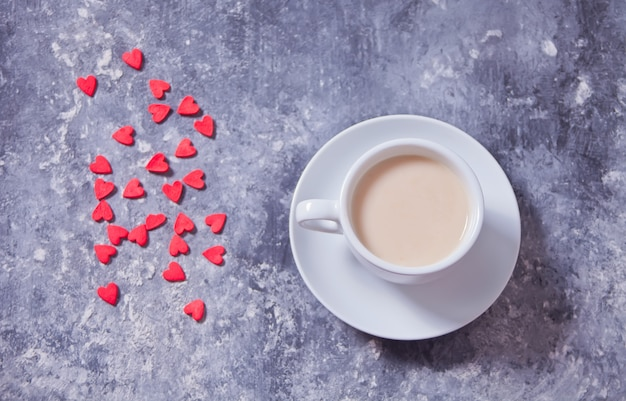 Heart-shaped red candy and a cup of coffee on a concrete background