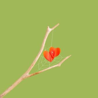緑の背景に乾いた木の枝に人工蜘蛛の巣のハート型の赤い花びら。最小限のコンセプト。水平方向の写真のレイアウト