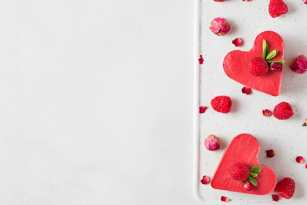 Heart shaped red raw vegan cakes with fresh raspberries, mint and dried flowers. valentines day dessert. top view