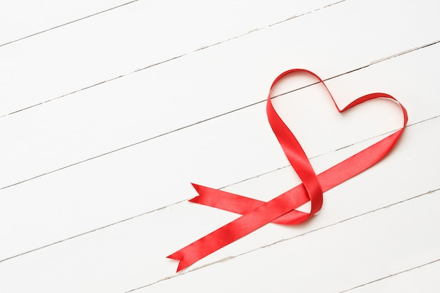 Heart-shaped red ribbon on white wooden background