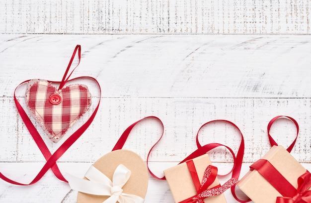 Лента и подарочная коробка в форме сердца на фоне белого деревянного стола с копией пространства. валентинка.
