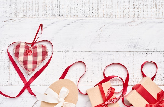 Heart shaped ribbon and gift box over white wooden table background with copy space. valentine day greeting card.